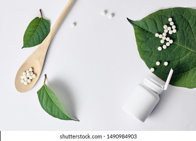 Homeopathy, naturopathy and alternative herbal medicine. Bottle with homeopathic pills on green plant leaf. Top view, flat lay with copy space over white background