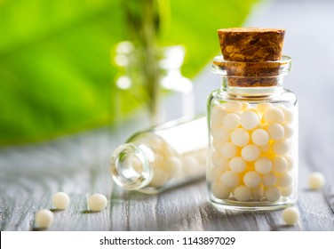Homeopathy pills bottle wooden eco green leaf background