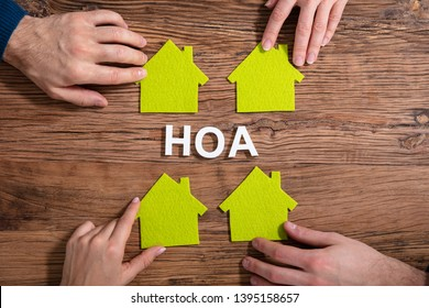 Homeowner Association Text Surrounded By People Holding House Model On Wooden Surface