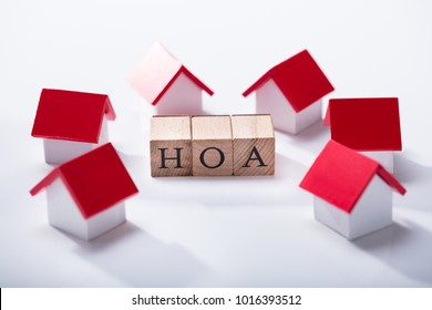 Homeowner Association Wooden Blocks Surrounded With Miniature House Models Over The White Background