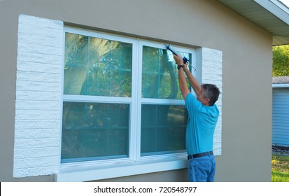 Homeowner caulking window with a caulk gun, an important part of weatherproofing homes and houses against rain, wind, hurricanes and storms.