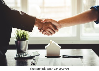 The homeowner is happy after receiving the transfer of the right to occupy the home. Agent and client shaking hands after signed document and done business deal for transfer right of property.