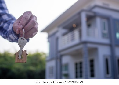 Homeowner holding a new house key from a broker after agreeing to buy a mortgage-home investment. Concept buying a house , a new home.