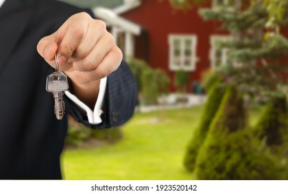 Homeowner holding a new house key from a broker. Concept buying a house.