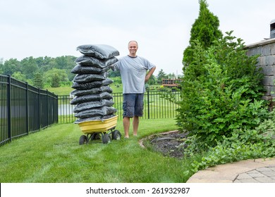 Homeowner Man Standing beside a Garden Wagon with a Pile of Bagged Mulch at the Backyard While Looking at the Camera.