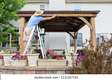 Homeowner staining a new gazebo in his backyard standing on a ladder painting the woodwork in DIY concept