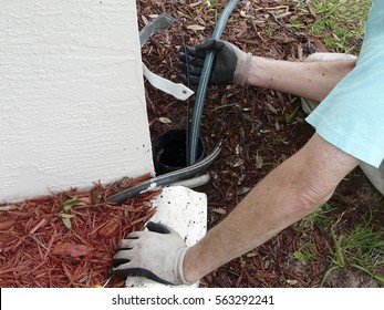 Homeowner uses sewer snake or rod to clear a blockage of dirt and leaves in the PVC pipe out to a point where water can be dispersed.