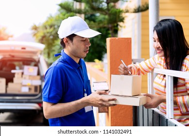 Homeowner woman receiving package from delivery man.signing to get her package.