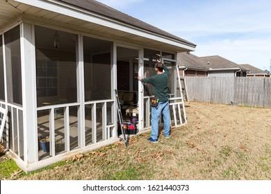 Homeowner works on repairing door to screened in back porch