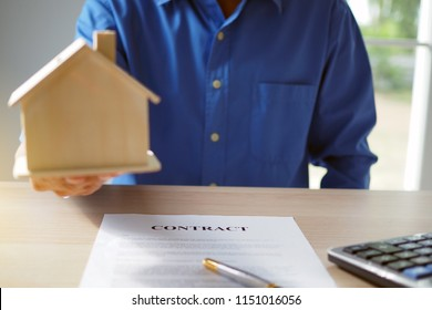 Homeowners are submitting home models. On the table are contract papers, pens and calculators. Home sales contract, house purchase and home rental concept