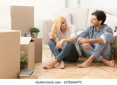 Homeownership. Young Couple Sitting On Floor Discussing Happy Future Into New Apartment. Copy Space