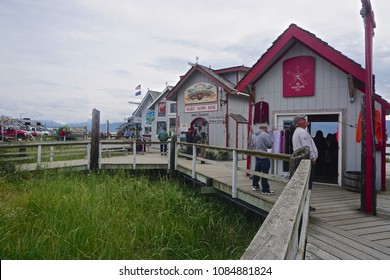 Homer, Alaska / United States - July 25, 2017: Tourists stroll the wooden boardwalk to visit the row of colorful shops at Homer Spit, in Kachemak Bay.