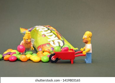 Homer Simpson and grandpa simpson using wheel barrow to collect skittles sweets