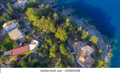 Homes above the ocean on a hill, overhead aerial view.