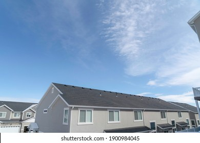 Homes in the suburbs with gray gable roof and sliding windows against blue sky