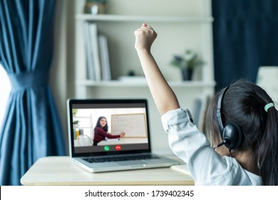 Homeschool Asian little young girl student learning virtual internet online class from school teacher by remote meeting due to covid pandemic. Female teaching math by using headphone and whiteboard. - Shutterstock ID 1739402345