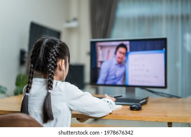 Homeschool Asian little young girl learning online class from school teacher by digital remote meeting due covid19 pandemic. Kid look to virtual video conference at computer laptop and study in house.