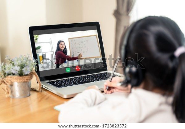 Homeschool Asian little young girl learning online class from school teacher by remote internet meeting application due to coronavirus pandemic. Female teaching math by using headphone and whiteboard.