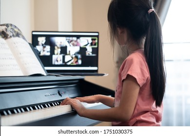 Homeschool Asian little young kid girl learning piano from computer connecting to internet music online class by school teacher. New normal lifestyle and education, student study at home concept.