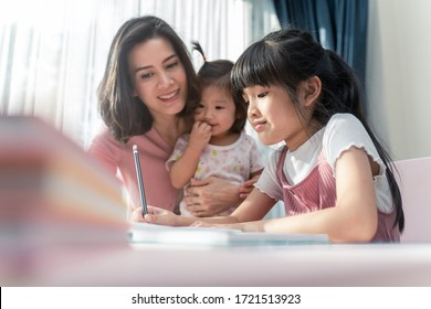 Homeschool Asian young little girls learning, reading and do homework while kind mother help and teach her. Mom and baby sister smile and encourage to girl. Girl happy to study at home education.