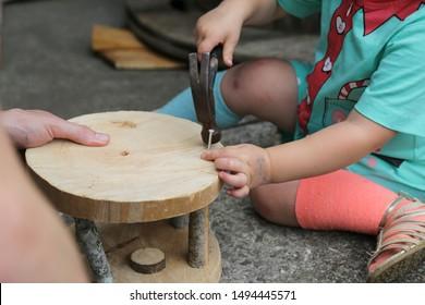 Homeschool children real life woodwork tools. Unschooling, rewilding. preschool, kindergarten. STEM science, technology engineering mathematics. Child building helping dad hammer and nail. Odd socks.