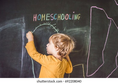 Homeschooling. Child pointing under word Homeschooling on a blackboard.