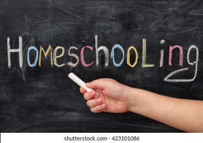 Homeschooling. Child pointing at word Homeschooling on a blackboard.