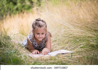 Homeschooling little girl reading the book on meadow in summer school during the holiday