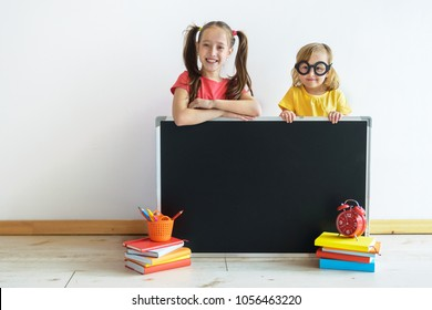 Homeschooling. The two kids  with a slate board against the background of a white wall. Education of children. Training of children in kindergartens and schools.