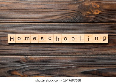 Homeschooling word written on wood block. Homeschooling text on wooden table for your desing, Top view concept.
