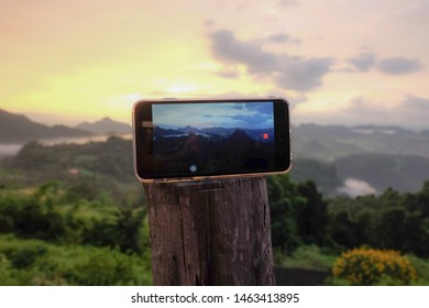 Homestay Ban Jo Bo, Maehongson, Thailand. 31 october 2018 :Is using an iPhone mobile phone to take a picture template of the sunrise with beautiful view, mountain and sky at Maehongson.