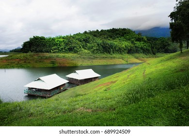 Homestay on Summer lake with green meadows around and blue cloudy sky