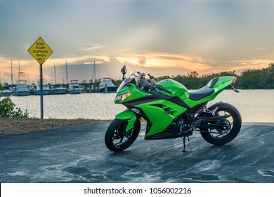 "Homestead, Florida / USA - July 10 2015: Lime Green 2015 Kawasaki Ninja 300 sport bike motorcycle during sunset at boat ramp with sign ""Slippery when wet"" with boats & piers in marina in background."