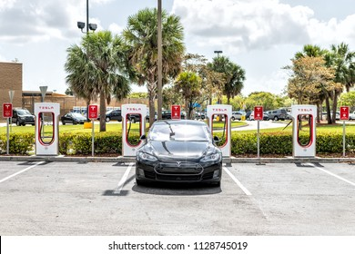 Homestead, USA - May 2, 2018: Closeup of Tesla Super Charging station in shopping mall with nobody, electric black car parked at parking lot