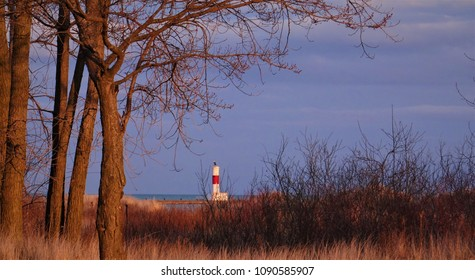 Hometown lakefront view of a lighthouse taken at the end of winter.  The calm before the storm of people.