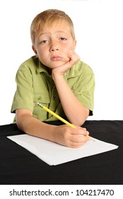 Homework is Boring. Seven year old boy sitting at a table not interested in doing his homework.