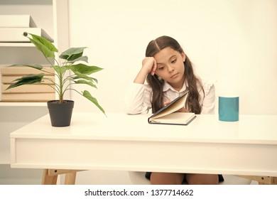 Homework concept. Girl do boring homework. Little child tired of doing homework at desk. Homework assignment.