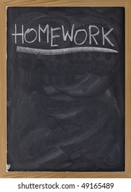 homework word handwritten with white chalk on blackboard with strong texture and smudge patterns, copy space below