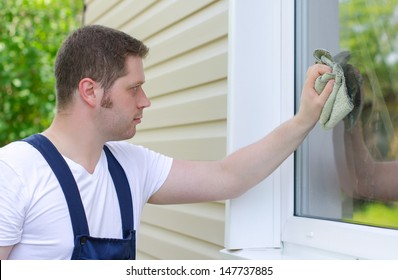 Homeworker with rag washing window outdoors