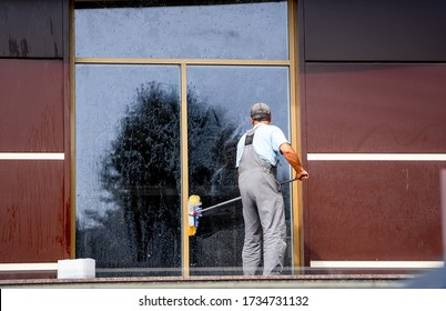 Homeworker with rag washing window outdoors. Professional cleaning. Big panoramic windows.