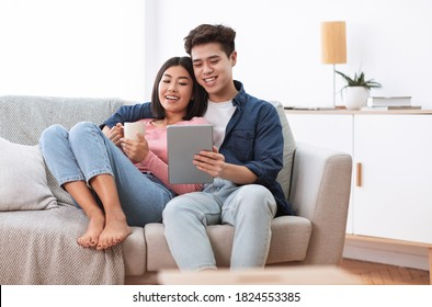 Homey Asian Couple Using Digital Tablet Watching Movie Online Relaxing On Weekend Sitting On Sofa At Home. Cozy Day-Off Together, Domestic Lifestyle Concept. Copy Space
