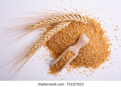 Hominy in a wooden spade and a sprig of wheat on a white background, top view.