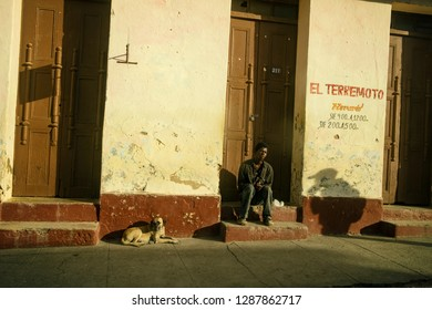 Homless man and dog waiting on street in Trinidad. Cuba. 01/31/2018