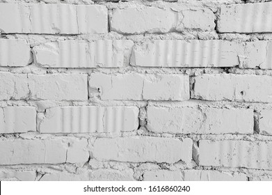 homogeneous background clean white brick wall with cracks from old age