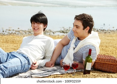 Homosexual couple enjoying themselves having a picnic at seaside