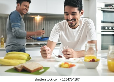 Homosexual couple, gay people, same sex marriage between hispanic men. Happy male partners eating breakfast and cooking in kitchen at home