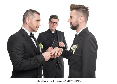 homosexual couple of grooms exchanging rings at wedding ceremony isolated on white