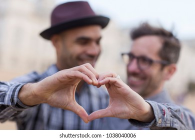 homosexual couple making a heart shaped symbol with their hands.