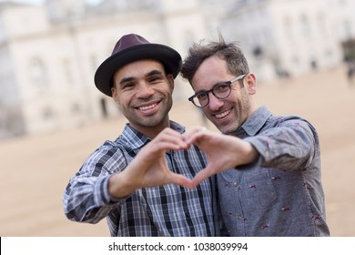 homosexual couple making a heart symbol with their hands.