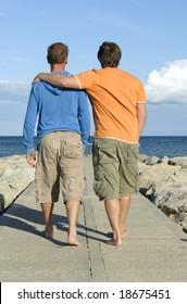 A homosexual couple take a leisurely walk along a beach pathway.